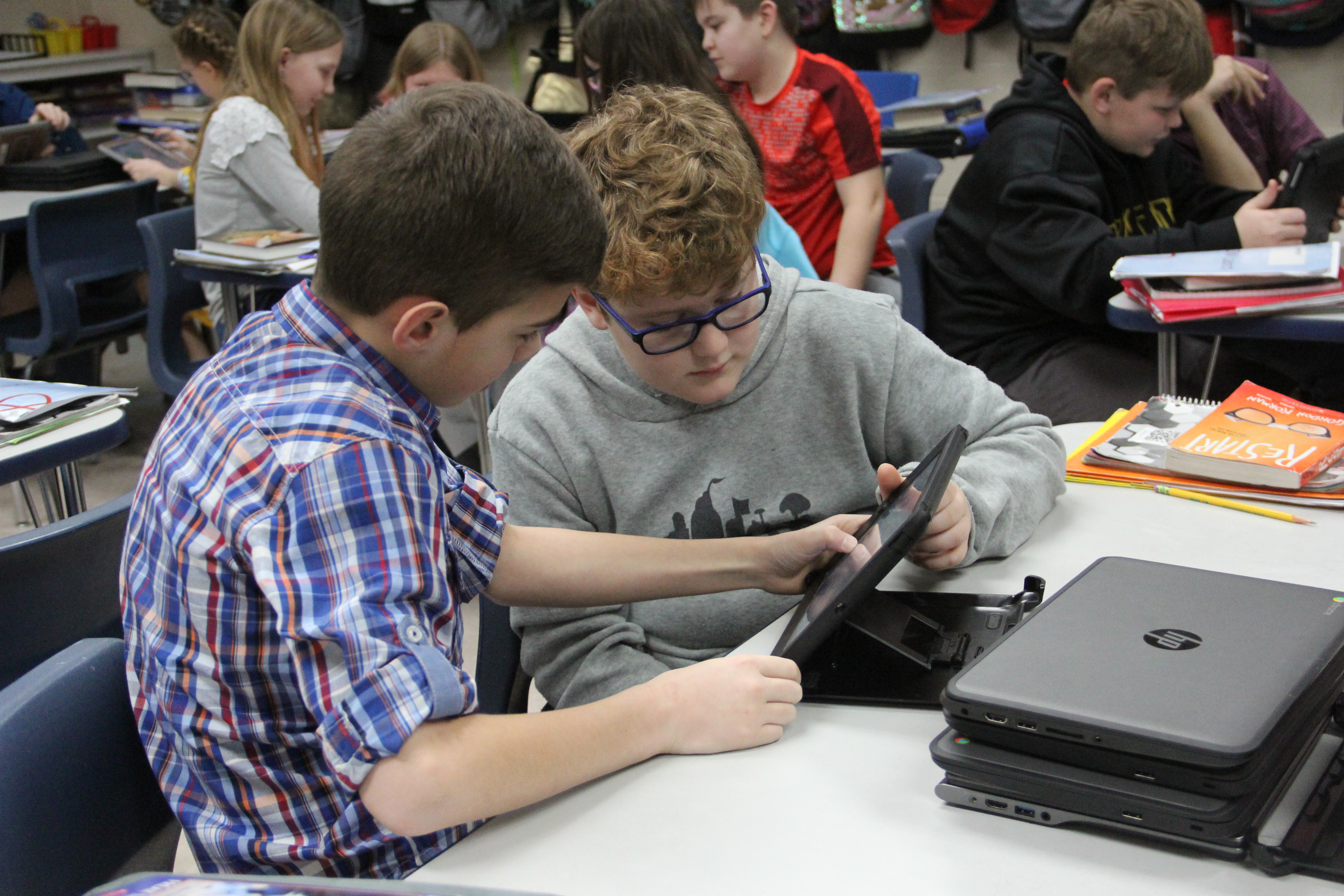 Two students using Ipads to complete a PLTW project.